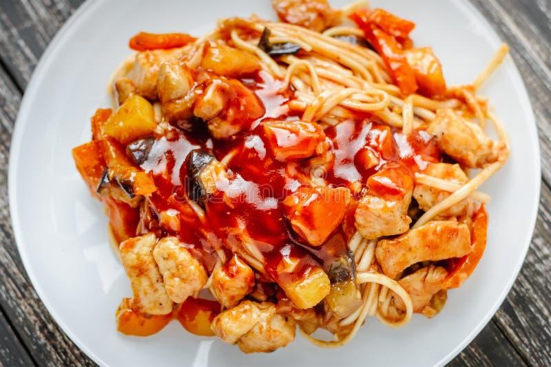 Udon braten Nudeln mit Huhn und Gemüse in der süß-sauren Soße an Traditionelle asiatische Küche lizenzfreie stockbilder
