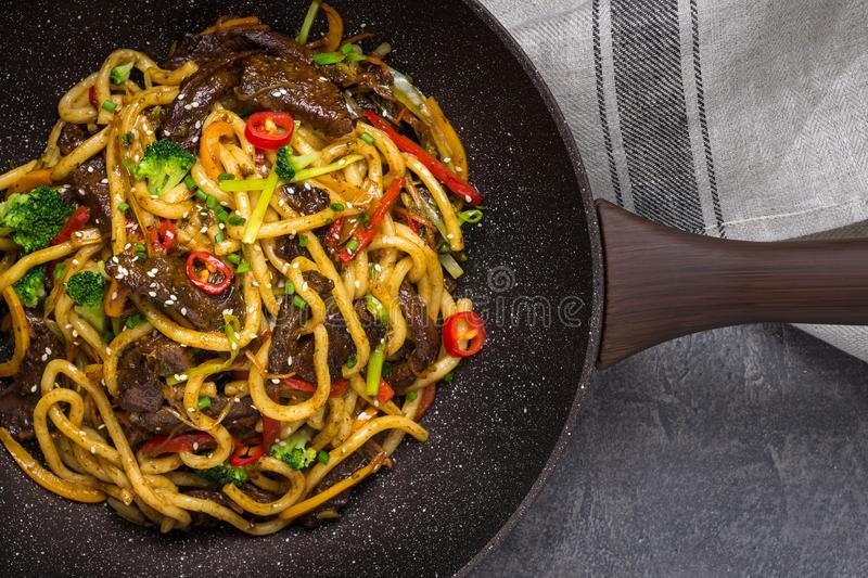 Udon Noodles with Beef and Vegetables in Wok Pan. Udon Stir-Fry Noodles with Beef and Vegetables in Wok Pan on Dark Background royalty free stock image
