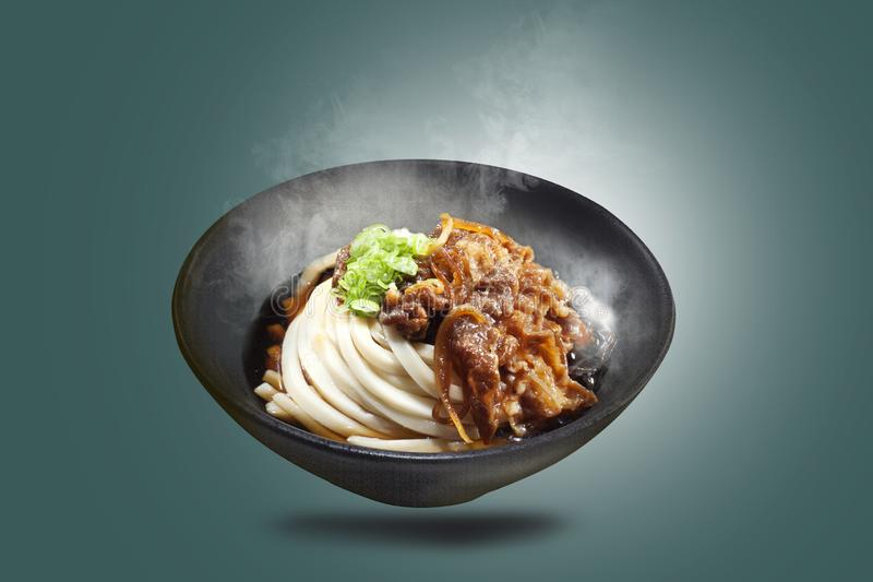 Udon noodles in black bowls are served with meat cooked with sliced onions, sprinkled with onion leaves royalty free stock photo
