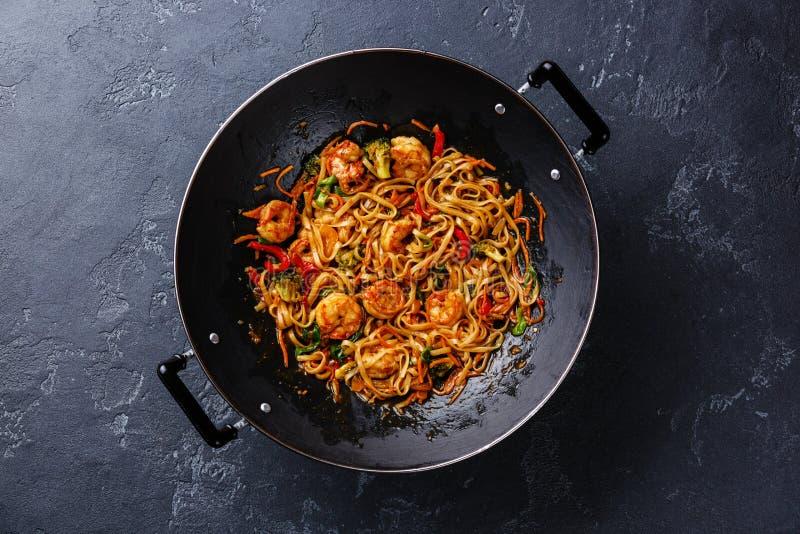 Udon noodles with shrimp in wok pan. Udon stir-fry noodles with shrimp in wok pan on dark stone background stock photos