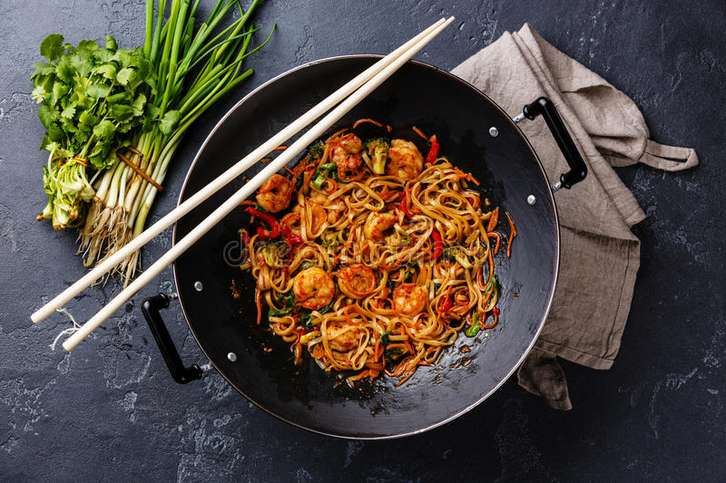 Udon noodles with shrimp in wok pan stock photography