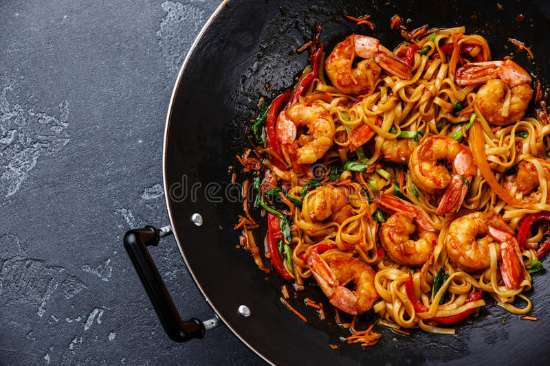 Udon noodles with shrimp in wok pan stock photo