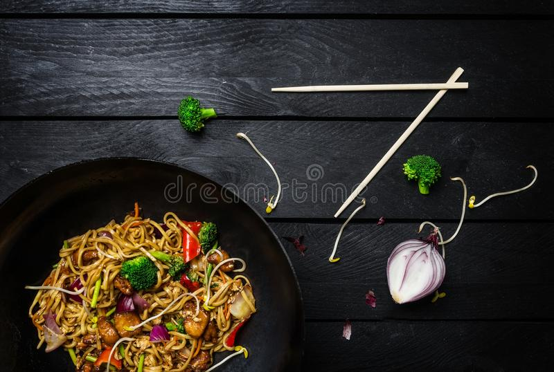 Udon stir fry noodles with chicken and vegetables in wok pan on black wooden background with chopsticks. Top view stock photography
