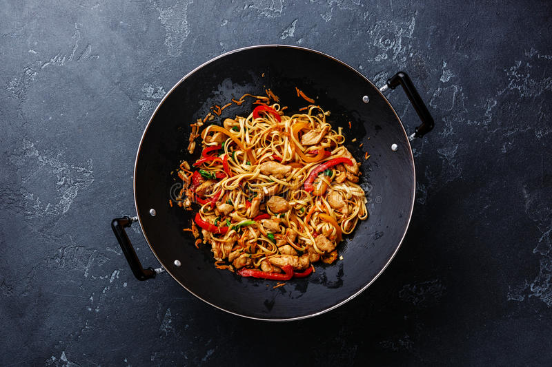 Udon stir-fry noodles with chicken and vegetables. In wok pan on dark stone background royalty free stock photo