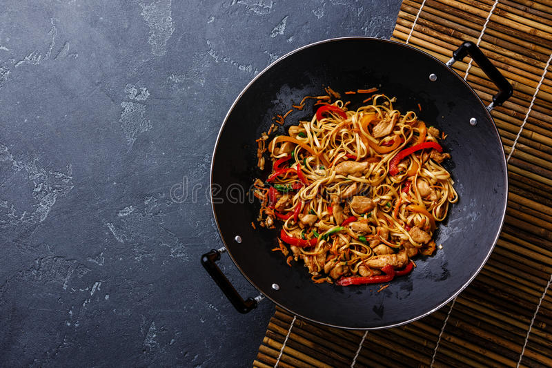 Udon stir-fry noodles with chicken in wok pan. Udon stir-fry noodles with chicken and vegetables in wok pan on dark stone background copy space royalty free stock photography