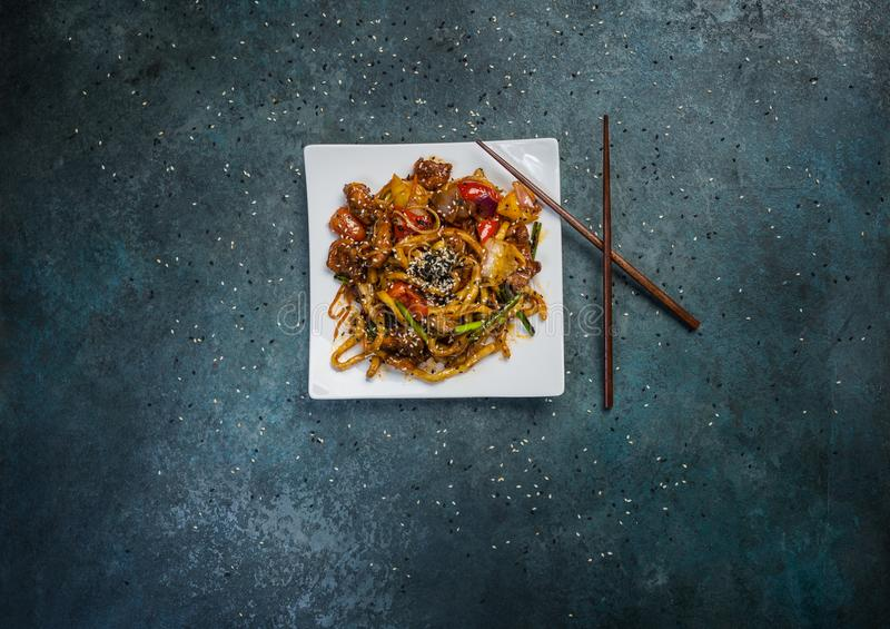Udon stir fry noodles with meat or duck, vegetables and sesame seeds on a square white plate. With chopsticks. stock images