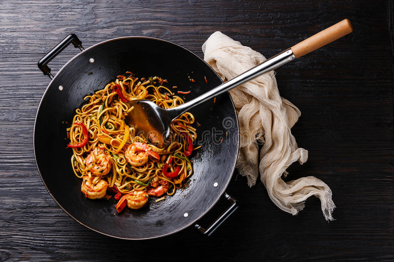 Udon stir fry noodles with prawn shrimp and vegetables in wok. Pan on black burned wooden background royalty free stock photo