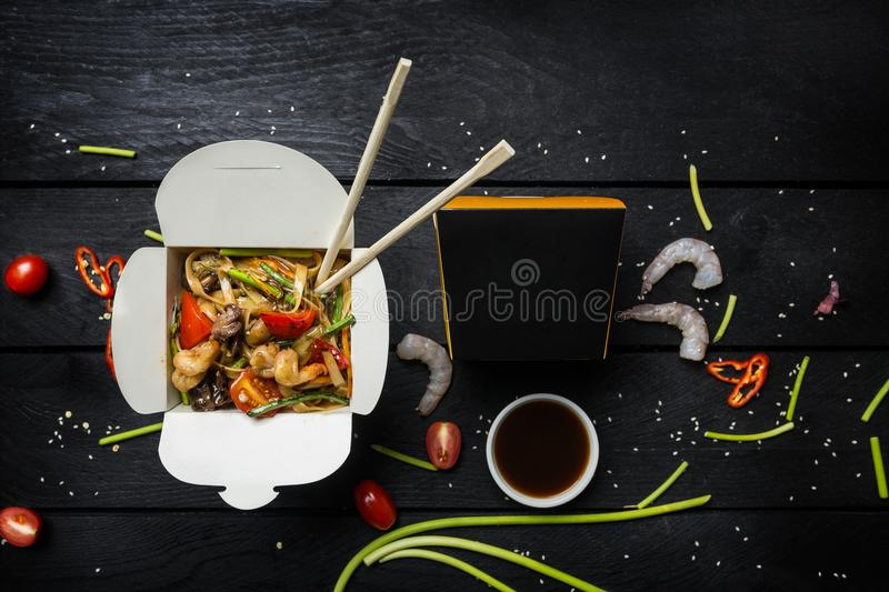 Udon stir fry noodles with seafood in a box on black background. With chopsticks and box for noodles. Udon stir fry noodles with seafood and vegetables in a box royalty free stock image
