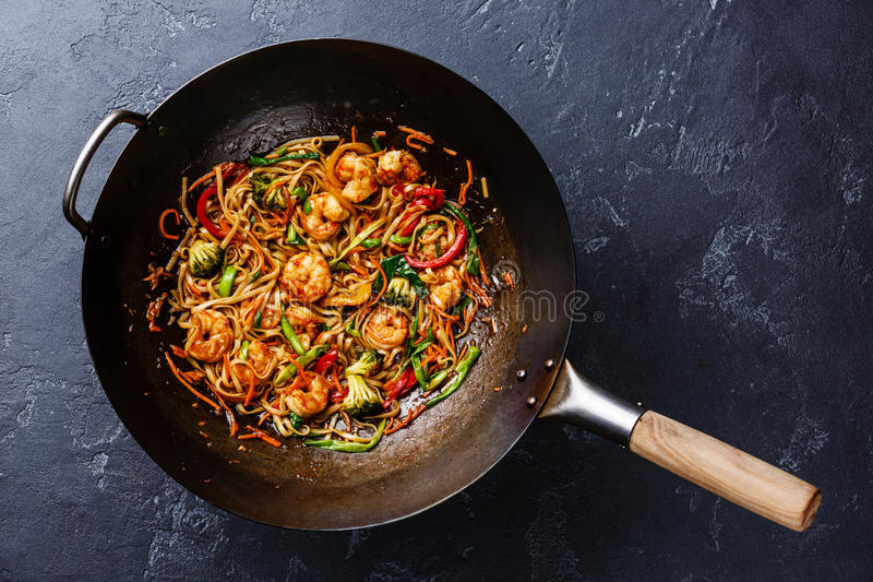 Udon stir-fry noodles with shrimp in wok pan. On dark stone background stock photo