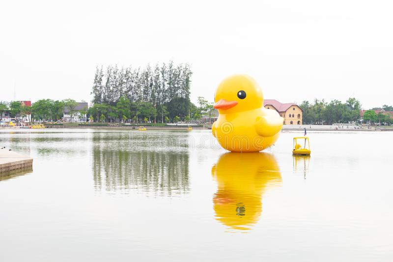 Ellow giant inflatable duck and yellow boat on the lake in Nong Prajak Park, Udon Thani royalty free stock photography