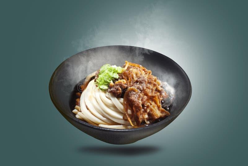 Udonnudeln in den schwarzen Schüsseln werden mit dem Fleisch gedient, das mit den geschnittenen Zwiebeln gekocht wird, besprüht m lizenzfreies stockfoto