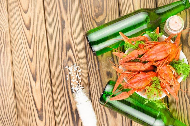 Udział gotowani czerwoni crayfishes i zielony świeży koper w białym ceramicznym pucharze obok dwa pełnych butelek piwo i rozprasz obrazy royalty free