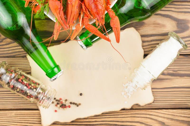 Udział gotowani czerwoni crayfishes i zielony świeży koper w białym ceramicznym pucharze obok dwa pełnych butelek piwo, rozprasza zdjęcie stock