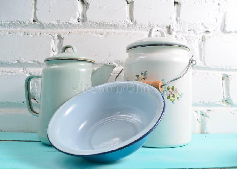 Udział emaliujący naczynia na błękitnym stole przeciw białemu ściany z cegieł tłu Retro stylowy cookware obraz stock