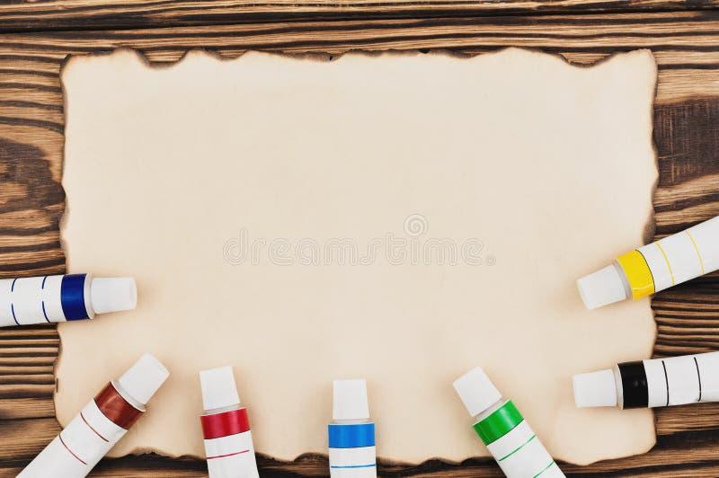 Udział kolorowe akrylowe farby w zamkniętych tubkach na burnt prostokąta pustym papierze obraz stock
