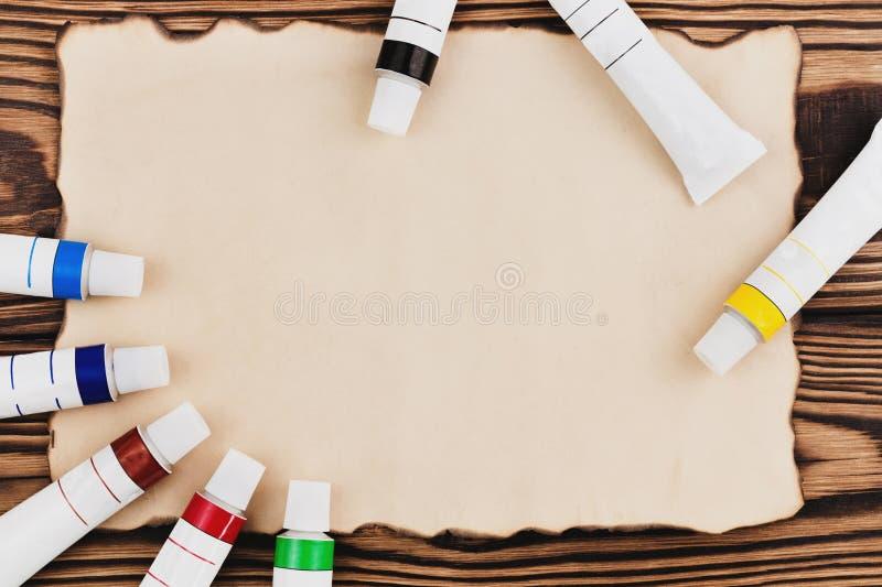 Udział kolorowe akrylowe farby w zamkniętych tubkach na burnt prostokąta pustym papierze zdjęcia royalty free