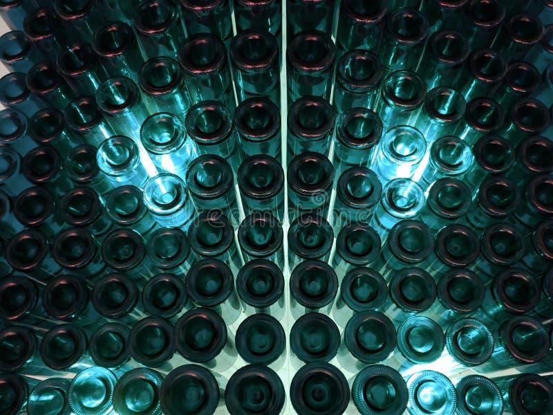 udział wino szklane butelki na pośrednim świetle w i ścianie kolorze, tle i teksturze błękitnych, obrazy stock