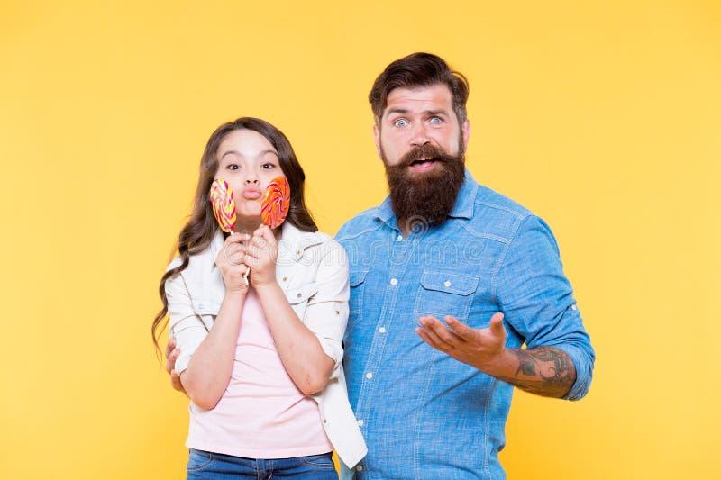 Udzielenie cukierki z kochanymi ludźmi Dziewczyny dziecko i taty chwyta kolorowi lizaki s?odki deser Brodaty modniś dobry zdjęcie royalty free