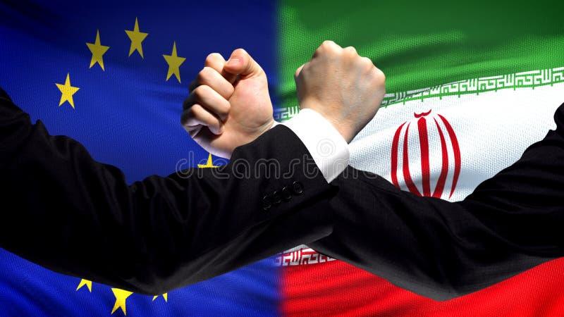 UE vs Iran konfrontacja, kraju nieporozumienie, pięści na chorągwianym tle obrazy stock
