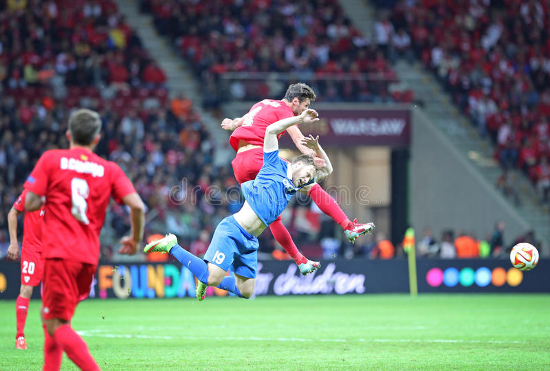 UEFA Europa League Final football game Dnipro vs Sevilla. WARSAW, POLAND - MAY 27, 2015: Roman Bezus of FC Dnipro (in Blue) fights for a ball with Grzegorz royalty free stock image