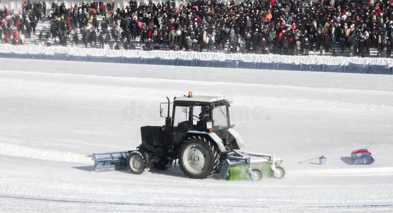 UFA, RUSIA - 12 de febrero de 2012: Hielo de limpieza del tractor en el estadio antes de la competencia del carretera fotos de archivo