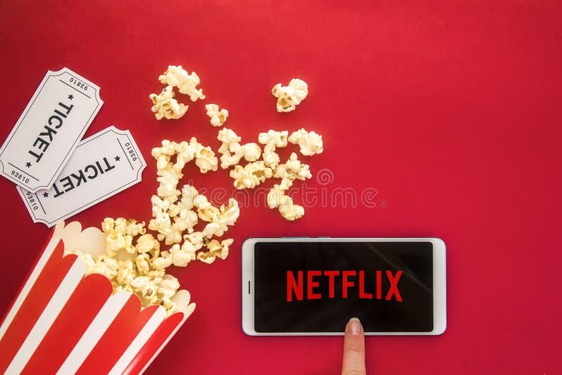 Ufa, Rusland - Jule 7, 2019: Tabel met popcorn-fles en Netflix-logo op smartphone Netflix is een globale leverancier van het stro royalty-vrije stock afbeeldingen