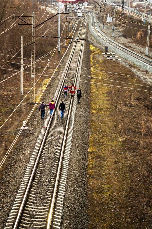 Ufa, Russia - 7 aprile 2019: i bambini vanno sulle piste del treno, i raggi del tramonto immagini stock