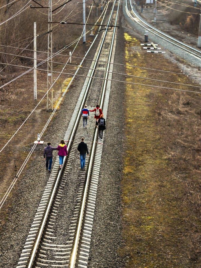 Ufa, Russia - 7 aprile 2019: un gruppo di adolescenti o gli scolari va sulle piste del treno, i raggi del tramonto immagine stock libera da diritti