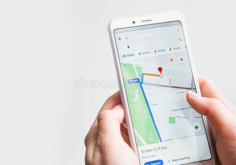 Ufa, Russia January 30, 2019: Female hand holding smart phone with Google map gps navigation application with planned route on the stock images