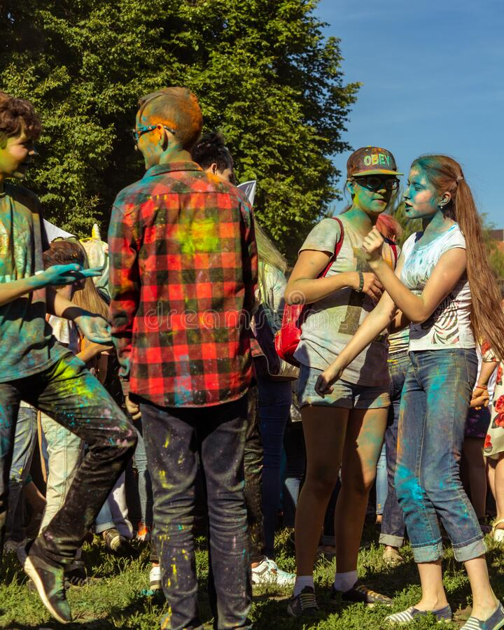 UFA, RUSSIA - 5 July 2019: teenagers at the festival of colors holi in paint divorces communicate, smile and have fun. Concept for Indian festival Holi. summer stock image