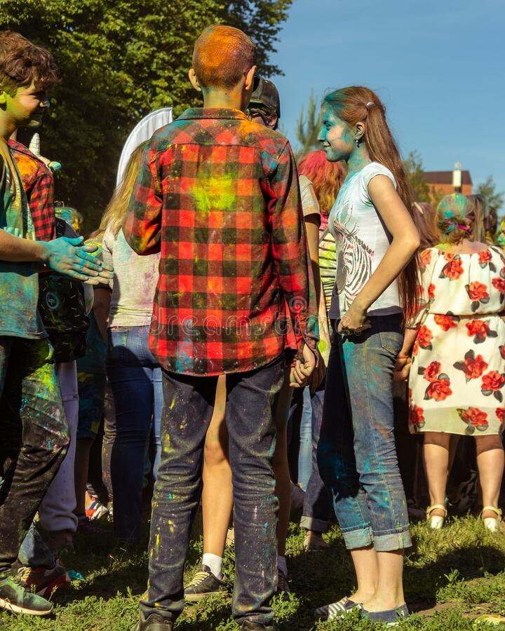 UFA, RUSSIA - 5 July 2019: teenagers at the festival of colors holi in paint divorces communicate, smile and have fun. Concept for Indian festival Holi. summer royalty free stock photography