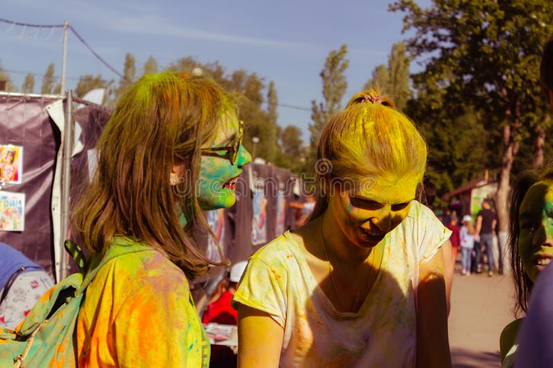 UFA, RUSSIA - 5 July 2019: two teenage girls with faces in holi paints at the summer paint festival communicate and smile. Concept for Indian festival Holi stock images