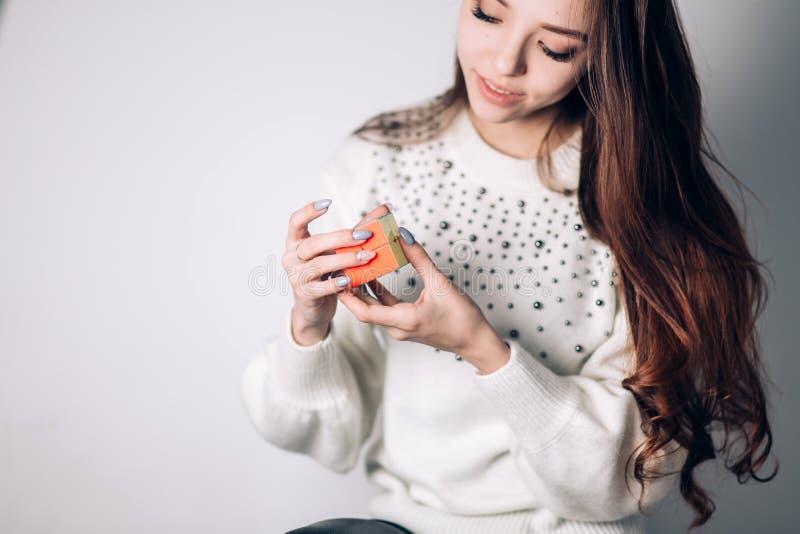 UFA, RUSSLAND - 14. JANUAR 2018: Schönes intelligentes Studentenmädchen löst Puzzlespiel, Rubiks Würfel und Lächeln auf weißem Hi stockfotografie