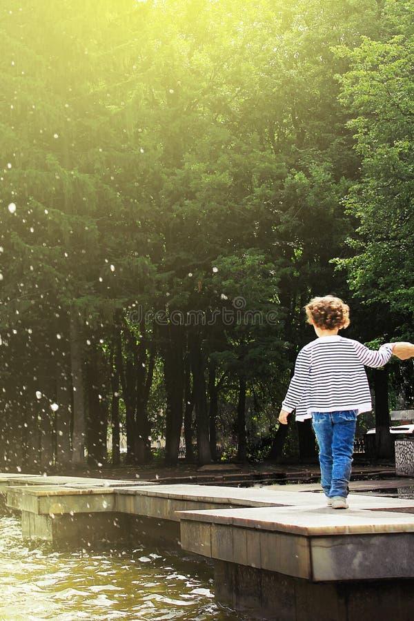 Ufa Ryssland - Juli 31, 2013: litet barn som promenerar kanten av springbrunnen som rymmer hans hand på bakgrunden av gröna tr arkivbilder