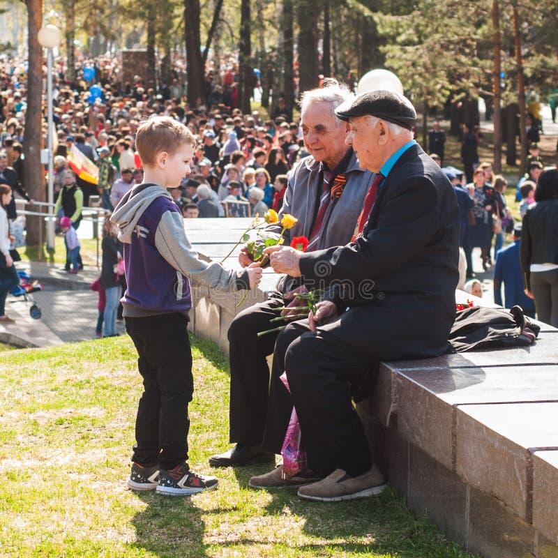 Ufa Ryssland-kan 09: pojken ger blommor till krigsveteran Segern ståtar royaltyfri bild