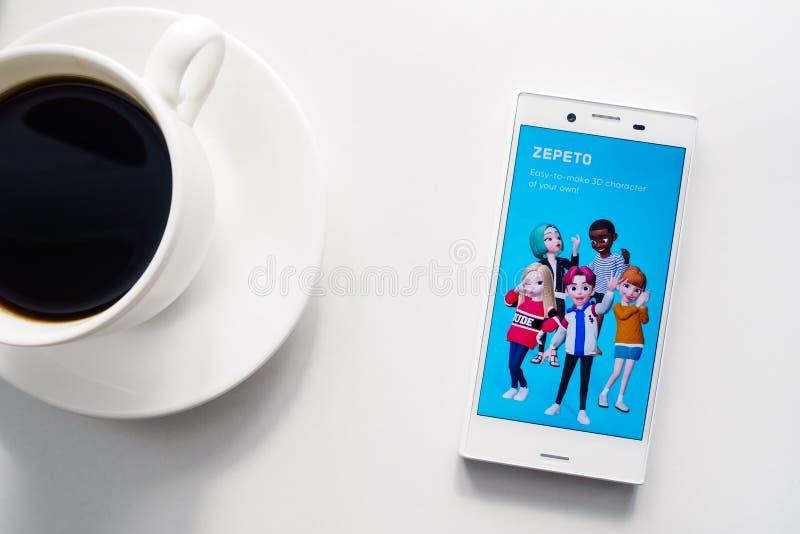 Ufa Ryssland - mars 15, 2019: ZEPETO-applikation på den Android smartphoneskärmen, telefonen och kaffekoppen på vit bakgrund arkivbilder