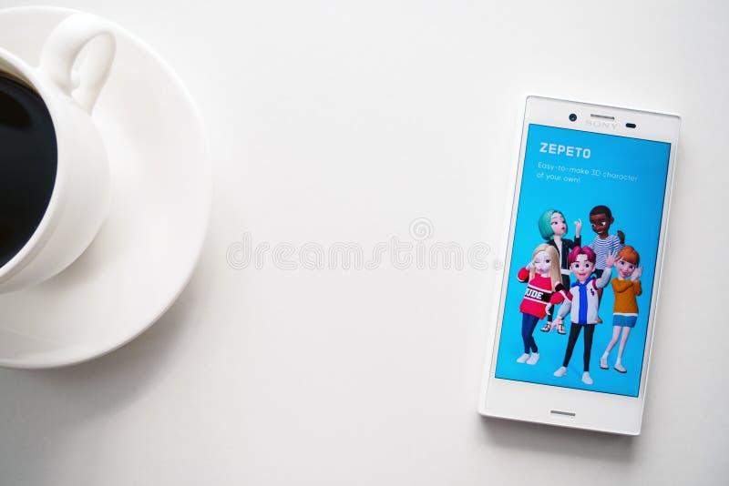 Ufa Ryssland - mars 15, 2019: ZEPETO-applikation på den Android smartphoneskärmen, telefonen och kaffekoppen på vit bakgrund, kop royaltyfria foton