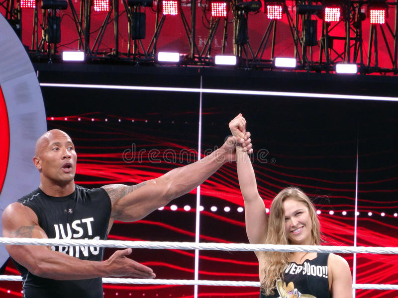 UFC star and Bantamweight Champion Ronda Rousey and the Rock celebrate by raising arms in the ring royalty free stock images