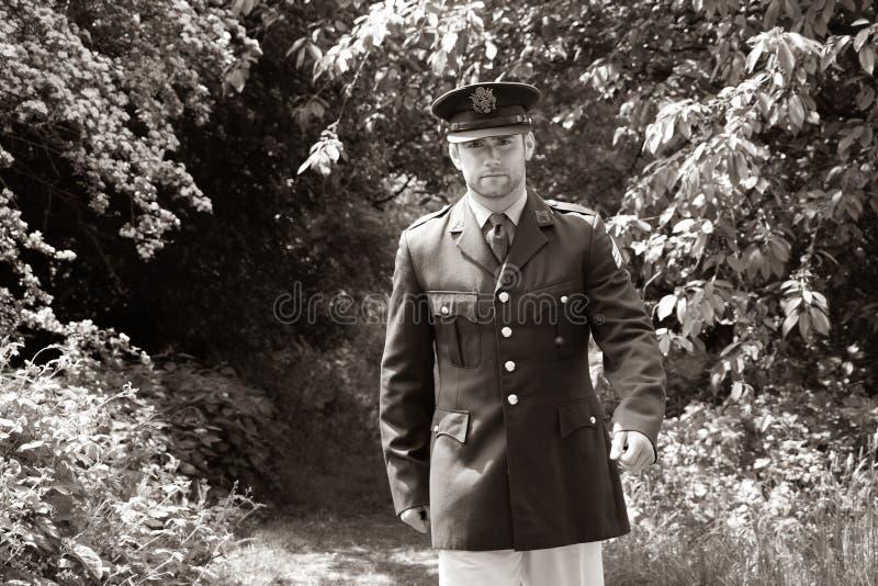 Ufficiale di esercito bello di GI dell'americano WWII in uniforme che cammina attraverso il legno immagini stock