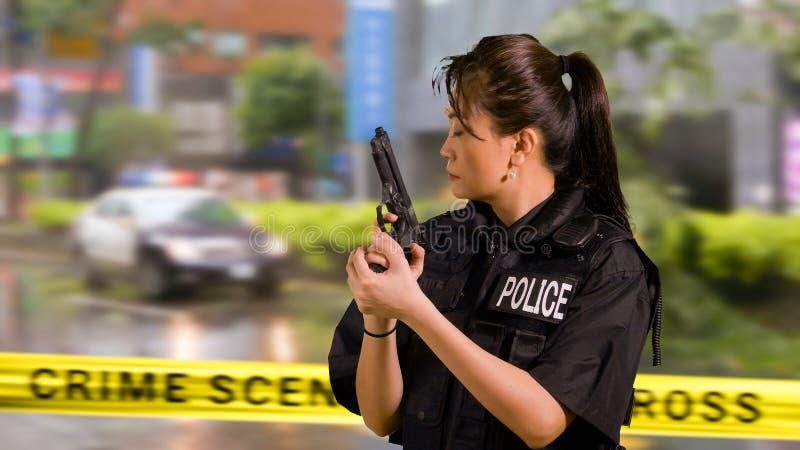 Ufficiale di polizia americano asiatico della donna alla scena del crimine, vista laterale, fotografia stock libera da diritti
