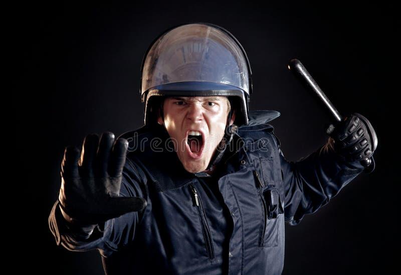 Ufficiale di polizia arrabbiato che dice folla violenta di fermarsi fotografie stock
