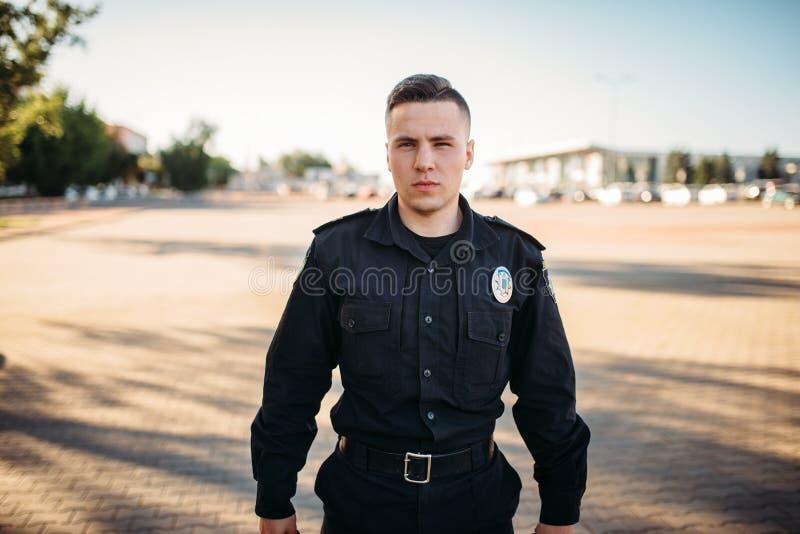 Ufficiale di polizia maschio in uniforme sulla strada fotografia stock