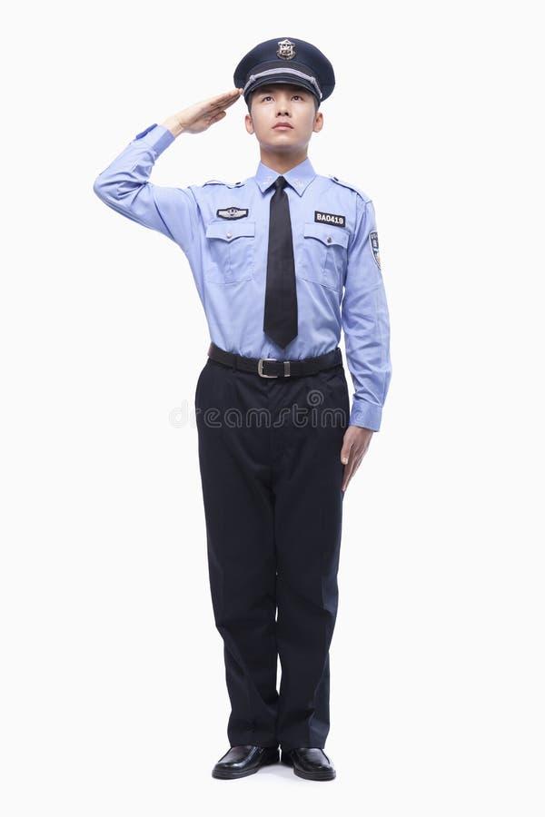 Ufficiale di polizia serio Saluting, colpo dello studio, integrale immagine stock
