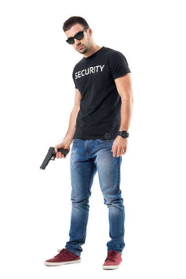 Ufficiale normale sicuro duro dei vestiti con gli occhiali da sole che tengono pistola che esamina macchina fotografica immagini stock libere da diritti