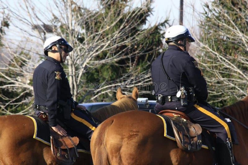 UFFICIALI DI POLIZIA AMERICANI DEI CAVALLI IN CITTÀ fotografia stock libera da diritti