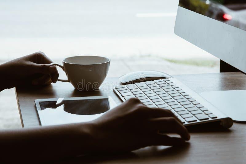 Ufficio che lavora alla tavola dell'ufficio con il posto di lavoro della tavola dell'ufficio di affari della tazza del computer e fotografia stock