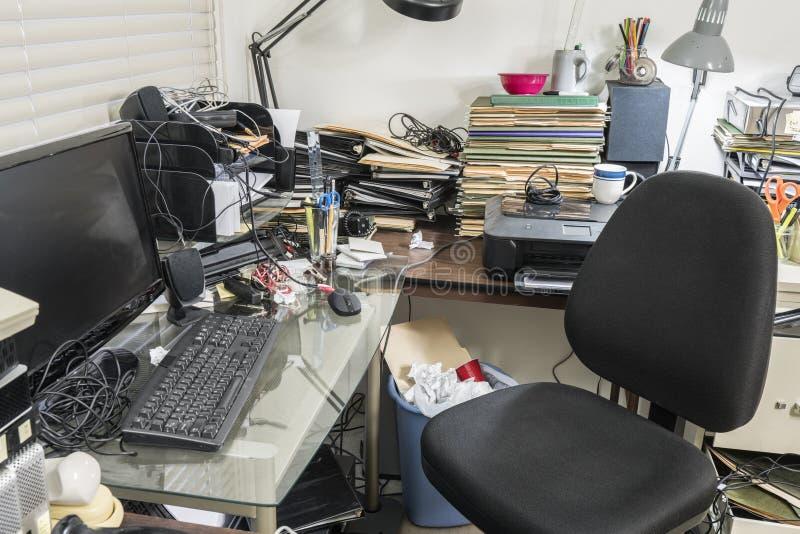 Ufficio con lo scrittorio sudicio pieno degli archivi e dell'ammasso immagini stock