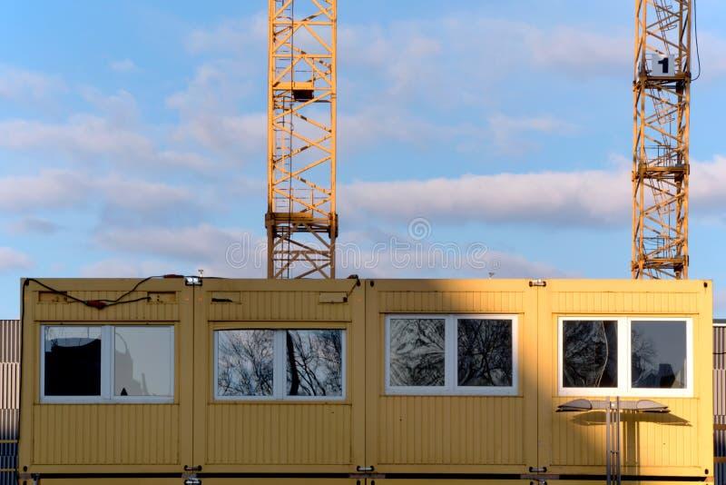 Ufficio del cantiere e un fondo di due gru gialle contro immagine stock libera da diritti