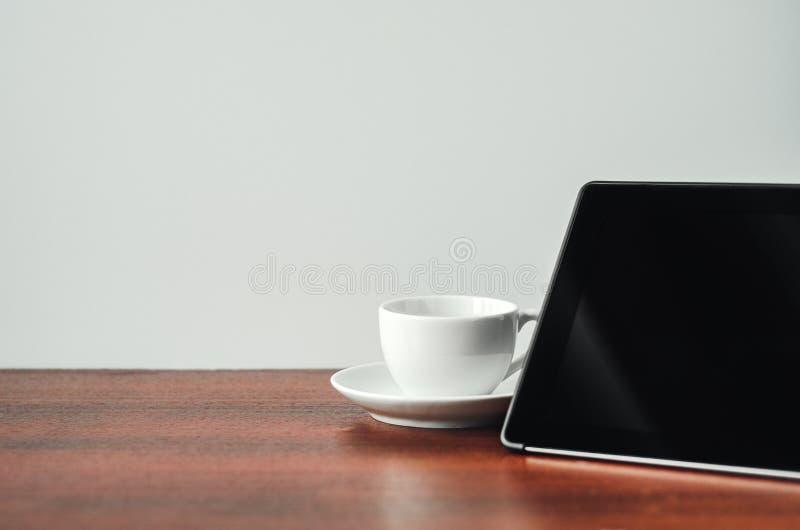 Ufficio dello scrittorio a casa Compressa nera, tazza bianca su una tavola di legno Concetto - lavoro a casa, free lance copi lo  fotografie stock libere da diritti