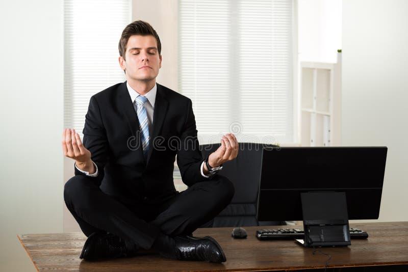 Ufficio di Doing Meditation In dell'uomo d'affari fotografie stock libere da diritti